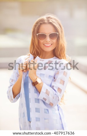 Attractive fashionable middle-aged woman standing in a street looking thoughtfully at the camera with a charming friendly smile. Toned image. - stock photo