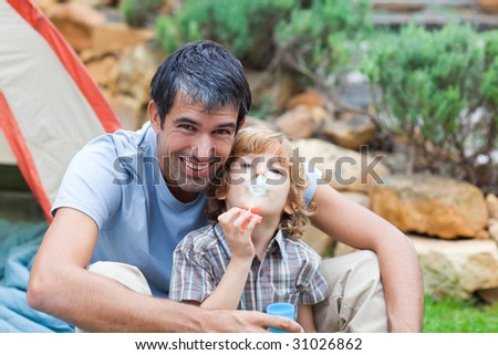 Attractive father and son playing in a tent - stock photo