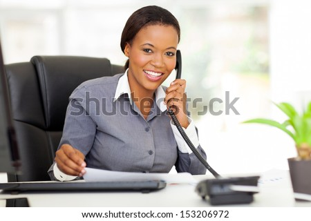 attractive female african office worker talking on phone - stock photo