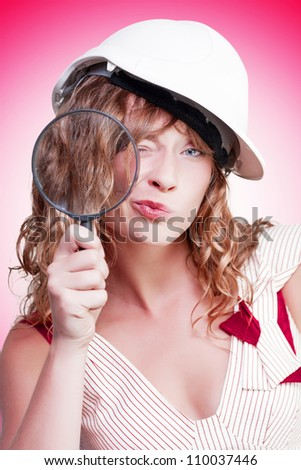 Attractive female building inspector wearing a hardhat while holding a large magnifying glass as she goes about her work expecting quality on the building site, conceptual studio portrait - stock photo