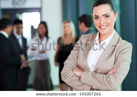 attractive female business executive with arms crossed in boardroom - stock photo