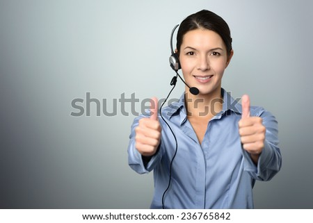 Attractive female call center operator, client services assistant or telemarketer wearing a headset looking at the camera and giving a thumbs up, on grey with copy space - stock photo