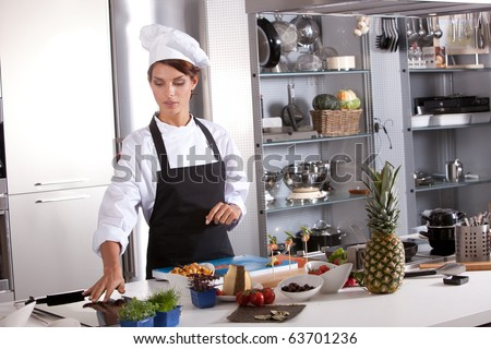 Attractive female chef working in her kitchen preparing the meal - stock photo