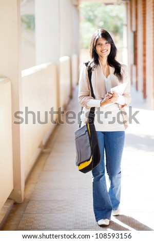 attractive female college student walking down school corridor - stock photo