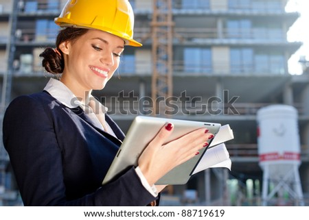 Attractive female construction specialist with a tablet computer at construction site - stock photo