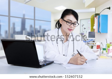 Attractive female doctor is writing prescription at the clinic - stock photo