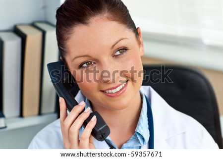 Attractive female doctor phoning in her office sitting at her desk