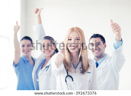 attractive female doctor with group of doctors showing thumbs up - stock photo