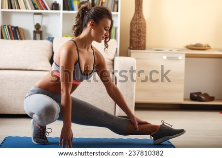 Attractive female doing exercise in her living room.She lifting a dumbbells.Workout. - stock photo