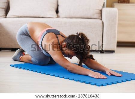 Attractive female doing exercise in her living room.She stretching her back.Workout. - stock photo