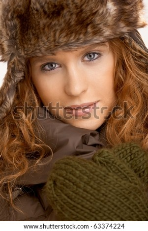 Attractive female dressed up in coat, scarf and fur- hat.? - stock photo