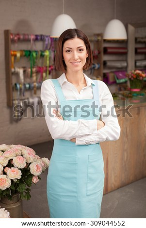 Attractive female florist is standing in her flower shop. The woman is smiling and looking at the camera happily. She crossed her hands - stock photo