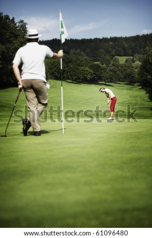 Attractive female golf player putting on green with second male player in the foreground holding the flag. - stock photo