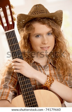 Attractive female hugging her guitar, dressed in western style.? - stock photo