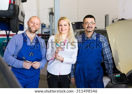 Attractive female insurance agent discussing with smiling auto mechanics renewal of car at workshop