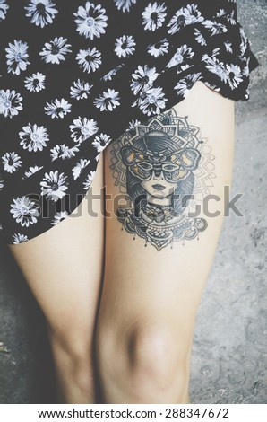 Attractive female leg with tattoo - stock photo