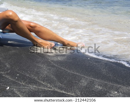 attractive female legs relaxing on a beautiful white and black beach   - stock photo