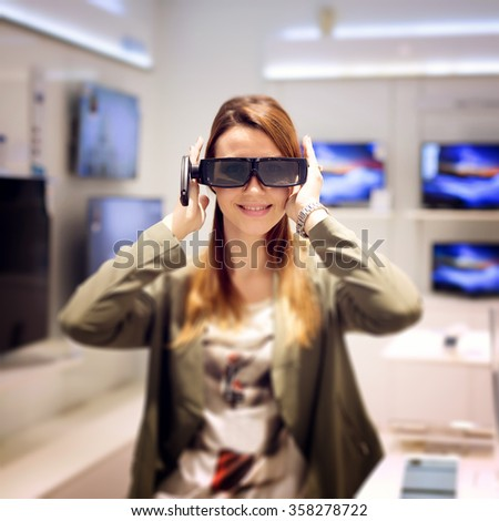 Attractive female looking for a new 3D tv. She is holding 3D glasses and looking at camera. Shallow depth of field. - stock photo