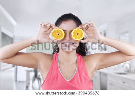 Attractive female model closes her eyes with two slices of healthy orange in the dining room at home - stock photo