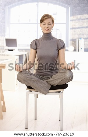 Attractive female office worker sitting at lotus position, meditating with closed eyes.? - stock photo