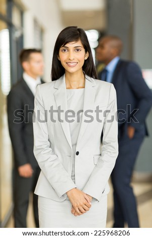 attractive female office worker with colleagues on background - stock photo