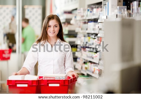 Attractive female pharmacist looking at camera in pharmacy setting. - stock photo