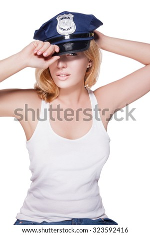 Attractive female police officer's cap on her head. Beautiful girl in a police cap on a white background with light make-up on her face. Girl holds hands behind his cap. police woman - stock photo