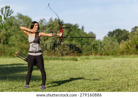 Attractive Female Practicing Archery At The Range - stock photo