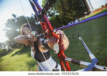 Attractive Female Practicing Archery At The Range. Focus Is On Bow - stock photo