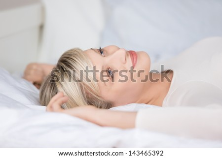 Attractive female relaxing on her bed in a close up shot - stock photo
