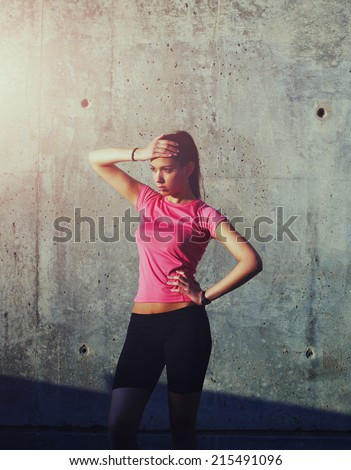 Attractive female runner on a break after running workout, beautiful athletic girl resting at sunset after intensive run outdoors, fitness girl resting after training outside, sports advertising - stock photo