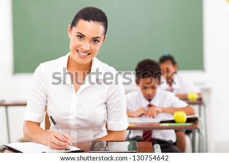 attractive female school educator preparing lessons in classroom