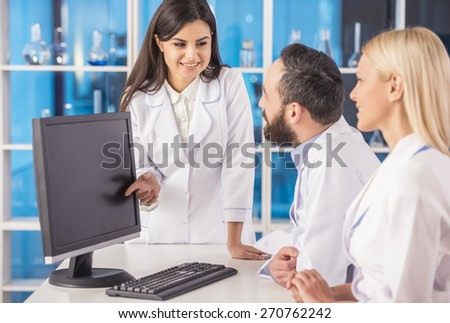Attractive female science showing her colleague sumething on computer. - stock photo