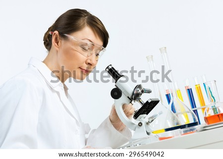 Attractive female scientist looking at the microscope slide in laboratory