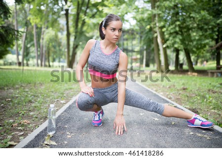Attractive female sport fitness runner getting ready for jogging outdoors.