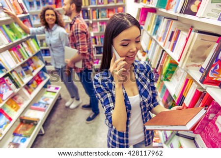Attractive female student is talking on the mobile phone while choosing book at the bookshop, young man and girl in the background - stock photo