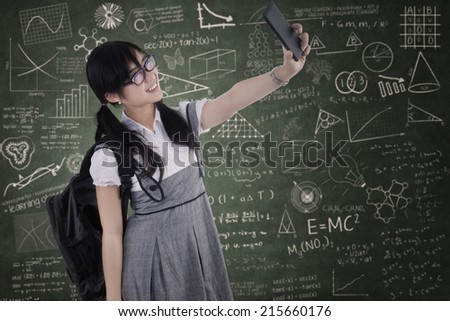 Attractive female student taking self portrait in the class