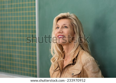 Attractive female teacher or university lecturer standing thinking in front of a blank blackboard looking into the air with a contemplative expression - stock photo
