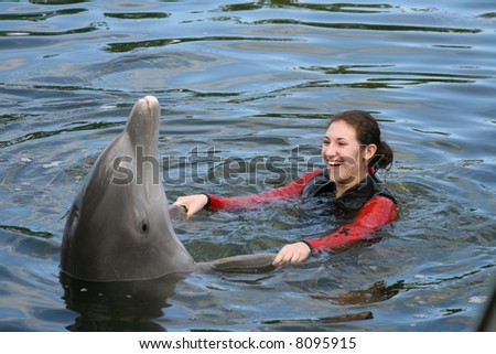 Attractive Female Teenager and a dolphin in the water - stock photo