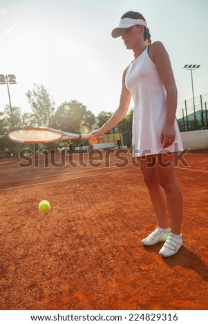 Attractive Female Tennis Player Holding A Racket And Hitting A Ball - stock photo