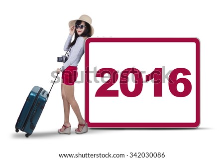Attractive female traveler leans on the board with number 2016 while carrying bag and digital camera - stock photo