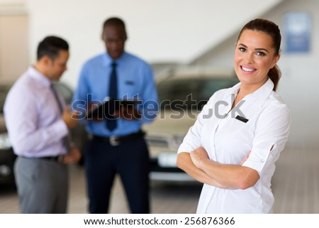 attractive female vehicle sales consultant standing in showroom - stock photo
