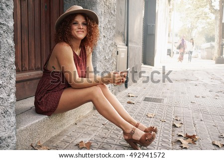 Attractive female with red curly hairs is sitting on a stair at the entrance door while texting to the friend by a mobile phone. Young girl with freckle face is sitting with a smart-phone on a street