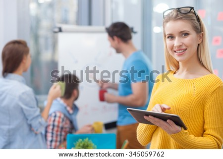 Attractive female worker is standing and using a tablet for work. Her colleagues are discussing the diagram on the board. The woman is looking at camera and smiling - stock photo