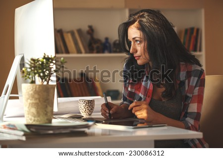 Attractive female working at home.Student.Using digital pen. - stock photo