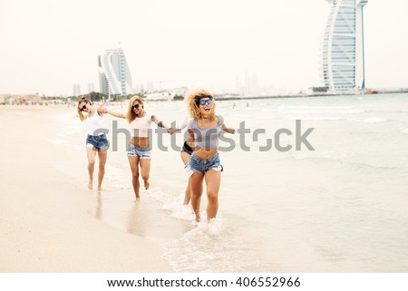 Attractive females holding hands and running at beach. - stock photo
