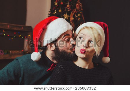 Attractive festive man giving girlfriend a kiss - stock photo