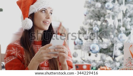 Attractive festive young woman in a Santa hat sitting in front of the Xmas tree checking for Christmas messages on her mobile phone