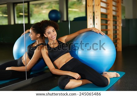 Attractive fit girl relaxing after fitness class sitting against big mirror at health center - stock photo