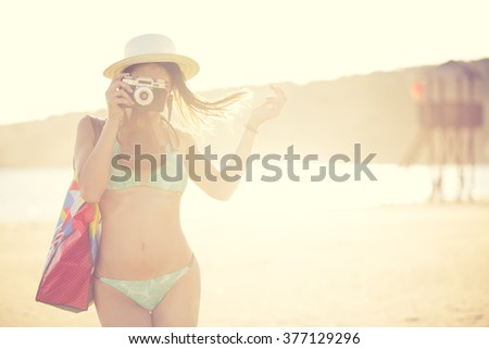 Attractive fit trendy modern hipster woman taking photos with retro vintage film camera.Lifestyle photographer.Summer beach woman taking picture during summer holiday vacation travel - stock photo